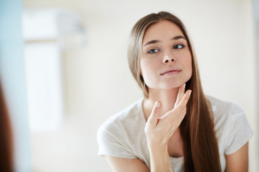 Young woman looking at her healthy skin in the mirror